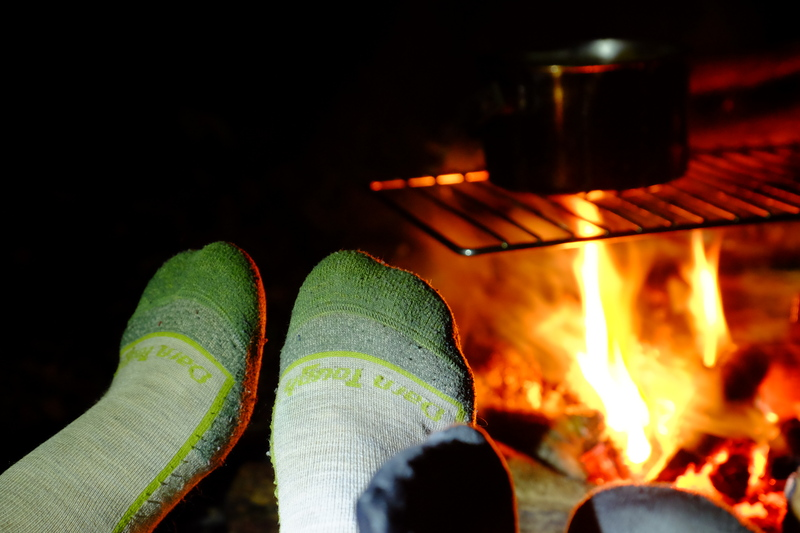 Socked feed warming by a camp fire